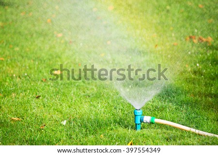Lawn sprinkler spaying water over green grass. Irrigation system in a yard