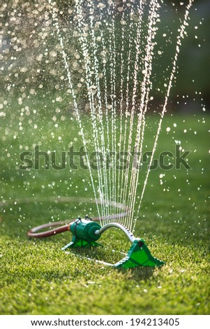 Lawn sprinkler spaying water over green grass. Irrigation system on a sunny summer day - stock photo