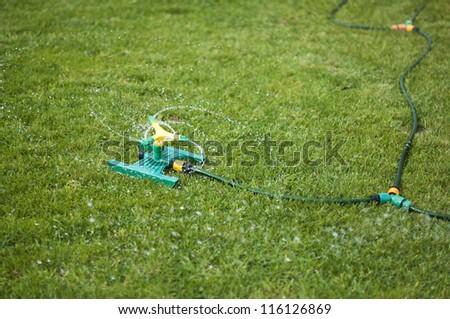 Lawn sprinkler splashing water over green grass. - stock photo