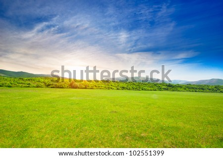 lawn with green grass, lush mountains in the background - stock photo