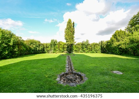 lawned garden and stone path with central Tuscan cypress - stock photo