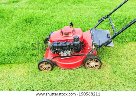 Lawnmower cutting grass in the garden - stock photo
