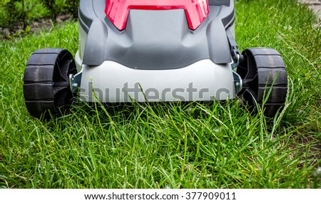 Lawnmower cutting grass in the garden