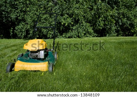 Lawnmower cutting green grass close-up with space for copy