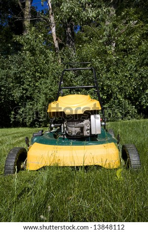 Lawnmower cutting long grass in a backyard, close up - stock photo