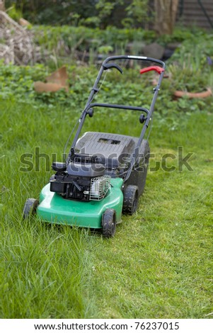 lawnmower. half cutted green lawn. - stock photo