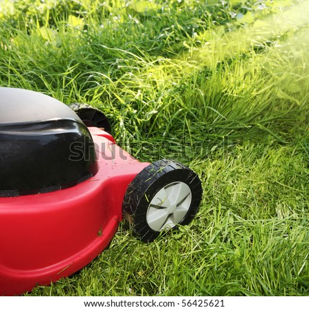 Lawnmower on green grass in sunny day - stock photo