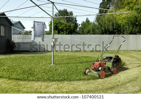 Lawnmower tied to a clothesline to create a clever and funny automatic lawnmowing invetnion. - stock photo