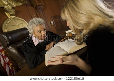 Lawyer communicating with judge in courtroom - stock photo