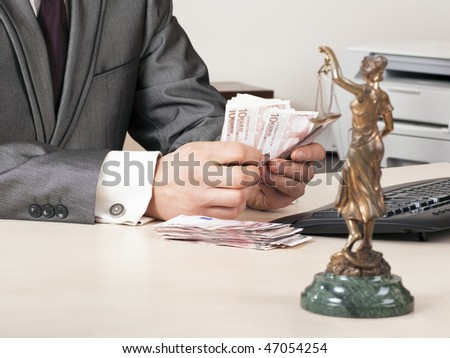 lawyer counts  the euro sitting on the desk opposite the statue of Themis