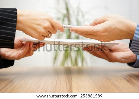 Lawyer gives woman contract and pen to sign - stock photo
