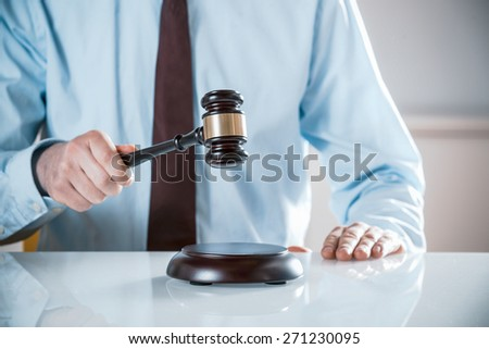 Lawyer, judge or auctioneer raising his wooden gavel to pass judgement or knock down a sale to the highest bidder, close up of his hands - stock photo