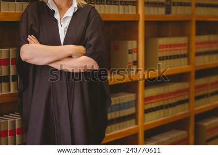 Lawyer leaning on shelf with arms crossed in library - stock photo