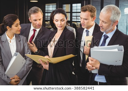 Lawyer looking at documents and interacting with businesspeople in office - stock photo