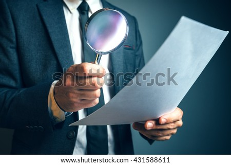 Lawyer reading legal contract agreement disclaimer with magnifying glass - stock photo