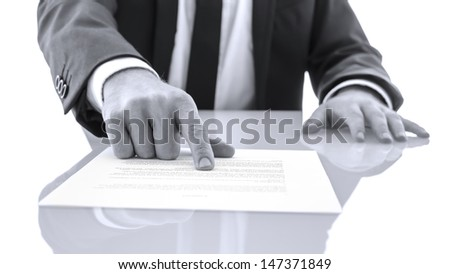 Lawyer sitting at white desk showing his client to proof read and check a statement. - stock photo