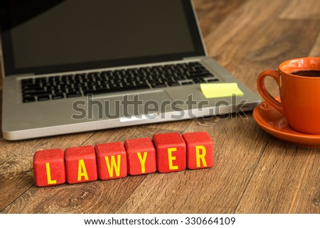 Lawyer written on a wooden cube in front of a laptop - stock photo
