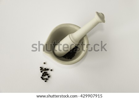 Lay flat image of ceramic mortar and pestle with black peppercorns on white background - stock photo