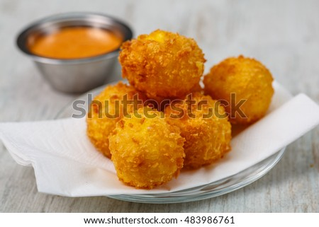 Lay the croquettes on a plate with red sauce. Big.