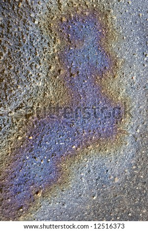 Layer of gasoline on a surface of wet asphalt as a sign of environmental contamination - a rainbow which does not bring pleasure - stock photo
