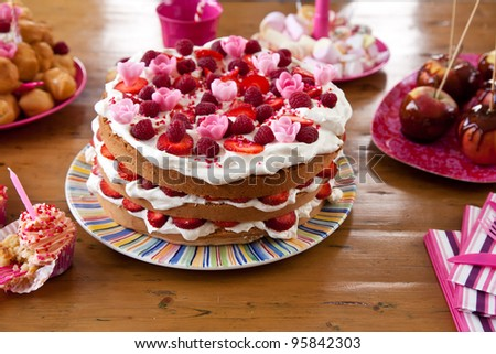Layered birthday cake amid other snacks on a table - stock photo