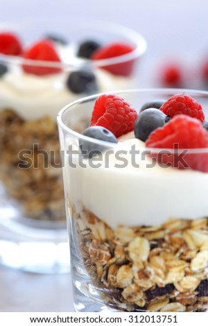 Layered breakfast cereal parfait style with yogurt and fresh berries