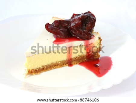 Layered cheescake case on white plate and background with plum sauce - stock photo