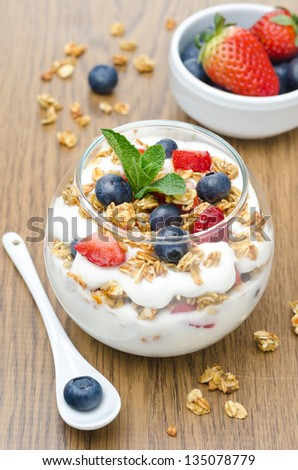 layered dessert with yogurt, granola, fresh berries garnished with mint on a wooden background closeup - stock photo