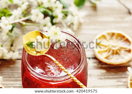 Layered homemade marmalade on the wooden background with cherry flowers, selective focus - stock photo