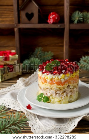 Layered salad from vegetables on the holiday table. Salad with walnuts, cheese, pomegranate and vegetables - stock photo