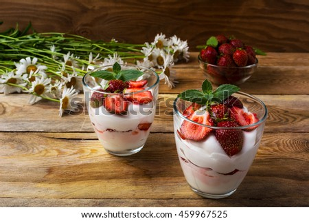 Layered strawberry yogurt dessert on wooden background. Diet yogurt dessert with ripe strawberry - stock photo