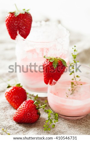 Layered vanilla and strawberry smoothie in glass jar, over old wooden table. Vintage effect, close-up