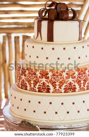 Layered white wedding cake with chocolate detail on silver serving dish - stock photo
