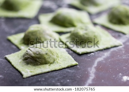 Layers green dough with spinach and mushroom stuffing for cooking pasta ravioli on table cuisine - stock photo