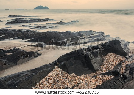 Layers of dark stone texture background on the beach with color tone - stock photo