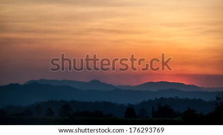 Layers of mountain at sunset with skyscrapers and colorful sky