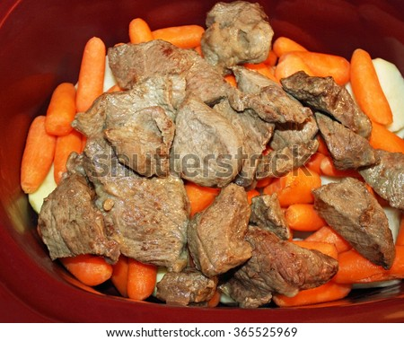 Layers of sliced white potatoes and carrots and browned stewing beef in a slow cooker  - stock photo