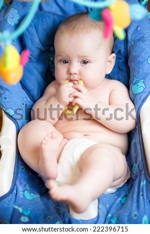 laying baby girl using teether - stock photo