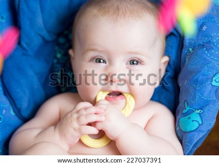 laying baby girl using teether toy top view - stock photo