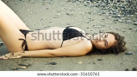 Laying beauty wearing black small bikini. - stock photo