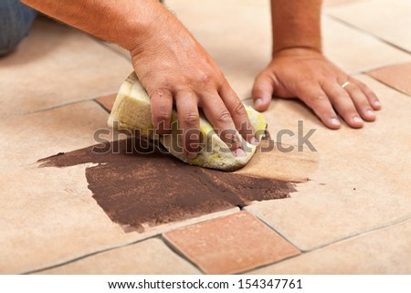 Laying ceramic floor tiles - man hands testing the color of joint on a small area - stock photo