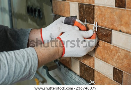 Laying Ceramic Tiles.Tiler aligns  seam between the tiles - stock photo