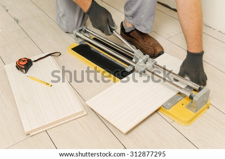 Laying Ceramic Tiles. Tiler cuts tile  manual cutter - stock photo