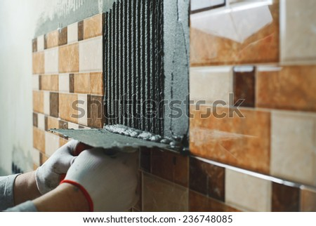 Laying Ceramic Tiles. Tiler deals tile adhesive on the wall - stock photo