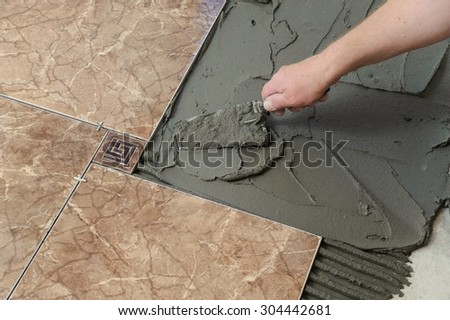 Laying Ceramic Tiles. Troweling adhesive onto a concrete floor in preparation for laying white floor tile. - stock photo