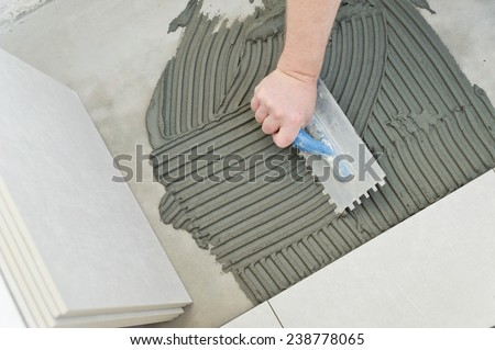 Laying Ceramic Tiles. Troweling mortar onto a concrete floor in preparation for laying white floor tile. - stock photo