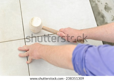 Laying Ceramic Tiles. Worker rap ceramic tiles for full bonding - stock photo