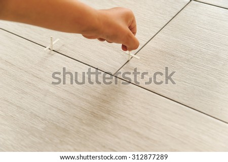 Laying Ceramic Tiles. Workers hand sets, plastic crosses between the tiles - stock photo