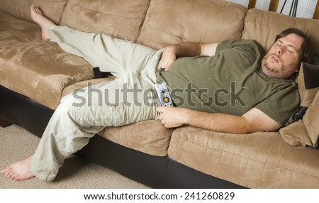 laying down on the couch with his hands down his pants a fat man is asleep - stock photo