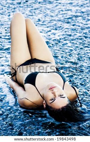 Laying green eyed beauty wearing black small bikini. - stock photo